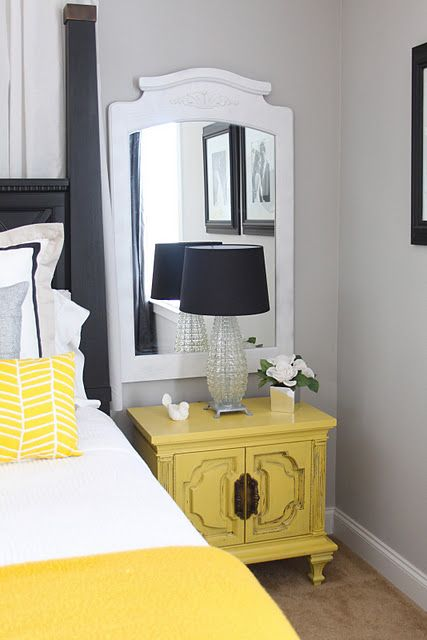 bedroom, brown rug flooring, white wall, white bedding, yellow pillow, yellow blanket, black bed platform, black covered table lamp, yellow cabinet, white mirror