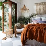 Bedroom, Chessboard White Grey Floor Tiles, White Wall, White Bedding, Orange Blanket, Rattan Pendant, Macrame, Plants, Wooden Chair With White Cushinos, Glass Wooden Door
