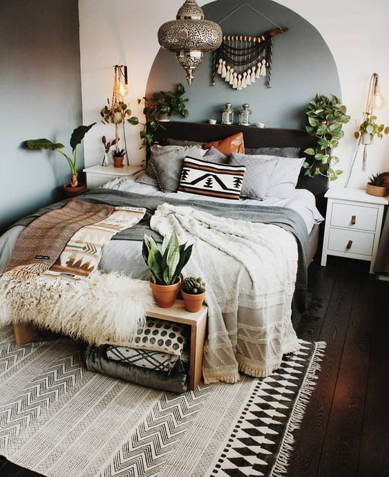 bedroom, dark wooden floor, white grey wall, grey bedding, dark wooden bed platform, white bedside table, simple wooden bench, pendant, plants