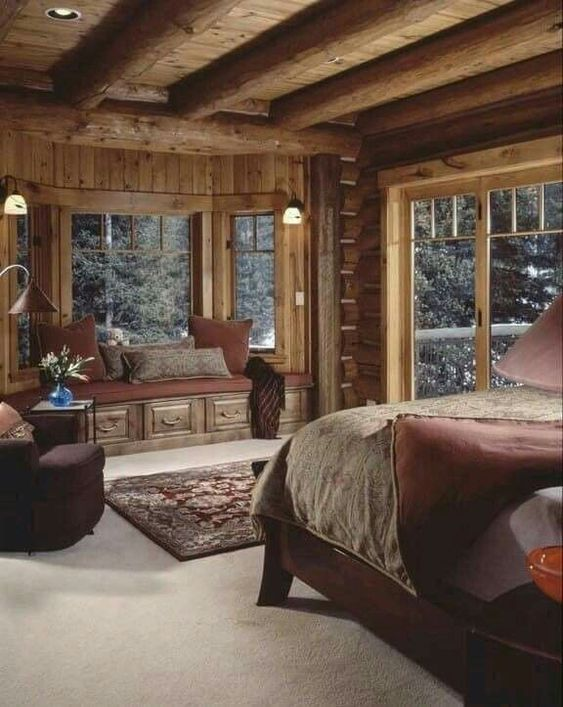bedroom, flat ceiling with wooden beams, rug, wooden bed platform, windows nook with wooden bench, brown cushion, brown chair, wooden wall, glass windows, sconces, floor lamp