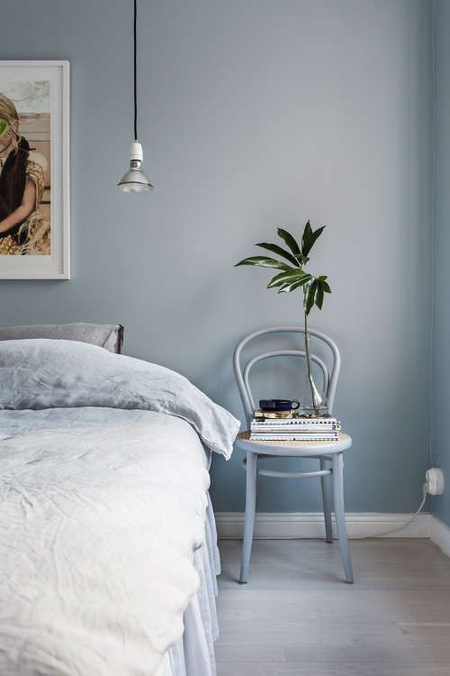 bedroom, light grayish blue wall, bedding, chair, wooden floor, pendant