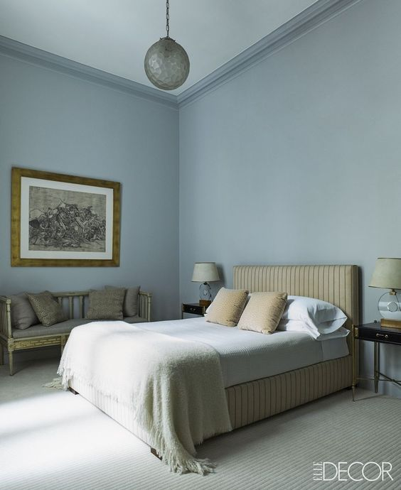 bedroom, muted light blue wall, beige bed platform, bench, light blue bedding, rug, pendant