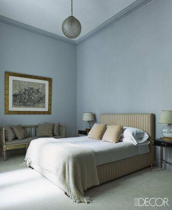 bedroom, muted light blue wall, beige bed platform, bench, light blue bedding, rug, pendant