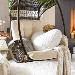 Bedroom Swing In Dark Rattan With Cushions, Pillows, Blanket, White Rug, Beige Wall