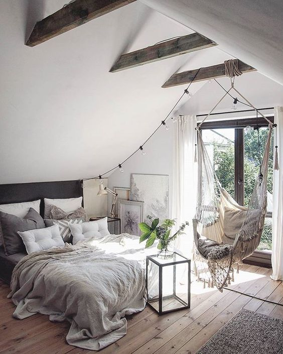 bedroom swing with fringes, pillow cushion, wooden floor, low bed, vaulted ceiling, wooden beams, rug, glass door