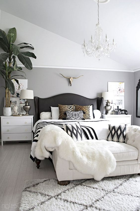 bedroom, white wooden floor, white rug, white bedding, black wooden bed platform, white sofa, grey white wall, white ceiling, chandelier, white wooden bedside cabinet