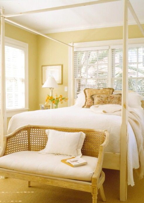 bedroom with soft yellow wall, bed platform with white bedding, wooden bench with white cushion, white table lamp