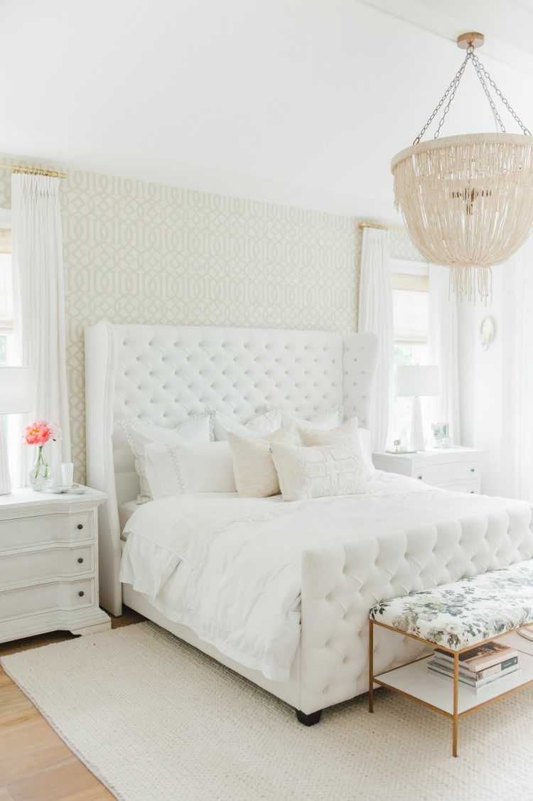 bedroom, wooden floor, beige rug, white bedding, white bed platform tufted, wraparound headboard, white bedside cabinet, chandelier