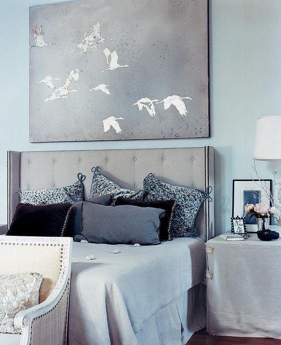 bedroom, wooden floor, blue painted wall, blue bedding, grey wraparound headboard, grey covered side table, yellow benh