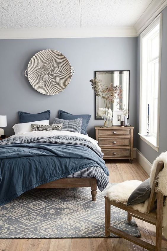bedroom, wooden floor, blue rug, blue bedding, wooden bed platform, light blue wall, white pattern textured ceiling, wooden bedsde cabinet, mirror, wooden chair