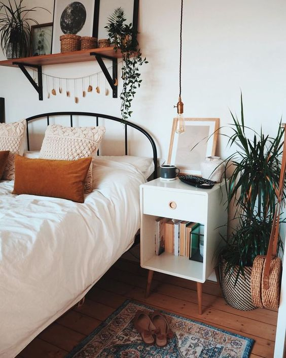 bedroom, wooden floor, rug, white wall, white bedding, black metal platform, floating shelves, white bedside shelves, plants
