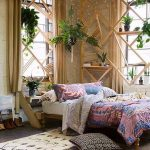 Bedroom, Wooden Floor, White Rug, White Bedding, Colorful Blanket Pillows, Beige Wall, Wooden Geometric Shelves And Decorations, Plants And Books,