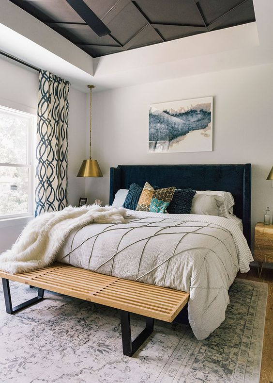 bedroom, wooden floor, white rug, white bedding, dark velvet headboard, wooden bench, golden covered pendants, white walls, statement ceiling