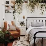 Bedroom, Wooden Floor, White Rug, White Wall, Black Metal Bed Platform With White Bedding, Plants On Floating Shelves, Brown Leather Chair, Ceiling Fan
