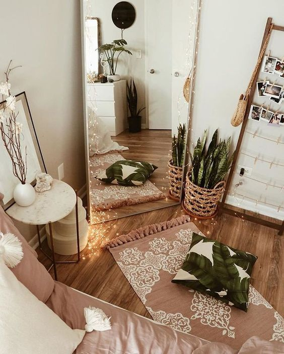 bedroom, wooden floor, white wall, tall mirror, wooden pictures displays, white side table, mauve bedding, small rug, white cabinet, plants on pots