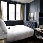 Black Tufted Wraparound Headboard, White Bedding, Black Wooden Wall, Black Painted Wall, Glass Window, Wooden Study Table, Black Wire Chair