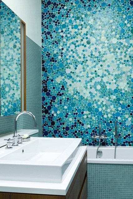 blue abthroom, blue tiny tiles on the tub, white inside tub, blue tiny mosaic on tub area, wooden cabinet, white sink