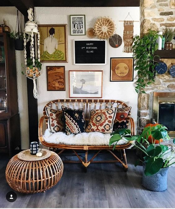 bohemian living room, ashen looked wooden floor, white wall, rattan sofa with white cushion, rattan round coffee table, wall accessories, plants, stone wall