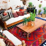 Bohemian Living Room, Red Patterned Rug, Wooden Carved Coffee Table, Sofa, And Chairs With White Cushion, Colorful Pillows, White Open Brick Wall, Moroccan Pendants