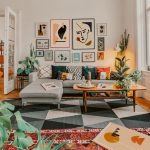 Bohemian Living Room, Wooden Floor, Geometric Grey Rug, Grey Sofa, Wooden Table, Colorful Pillows, White Wall, Wall Decorations, Orange Rug, Plants