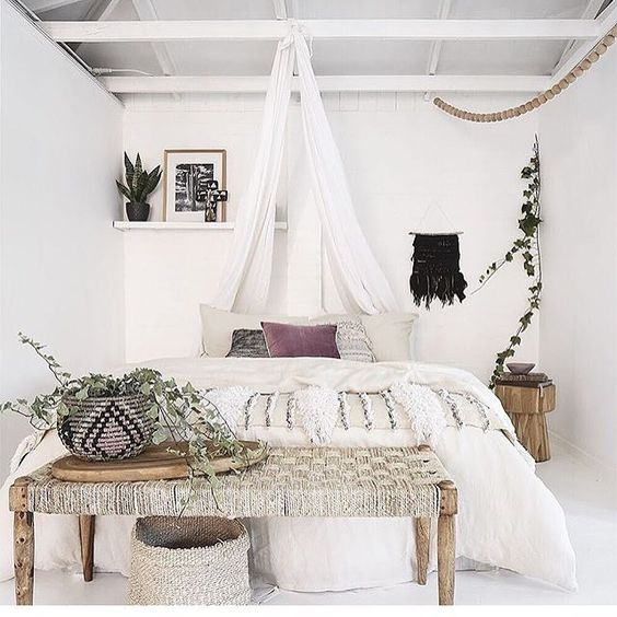 boho bedroom, white floor, white wall, white ceiling, white wooden beam, wooden bench with rattan seating, white bedding, curtain
