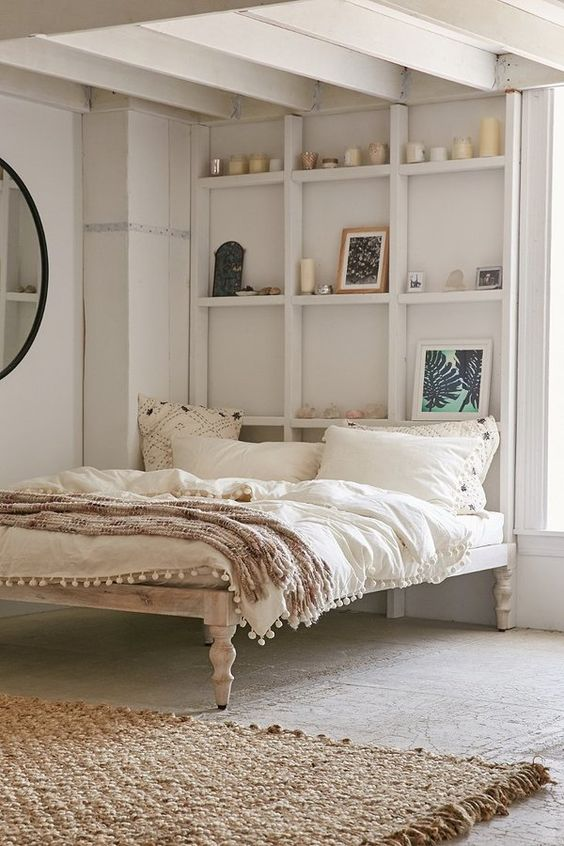 boho bedroom with grey floor, rattan rug, wooden boho bed platform, white built in shelves, round mirror, white bedding, white wall