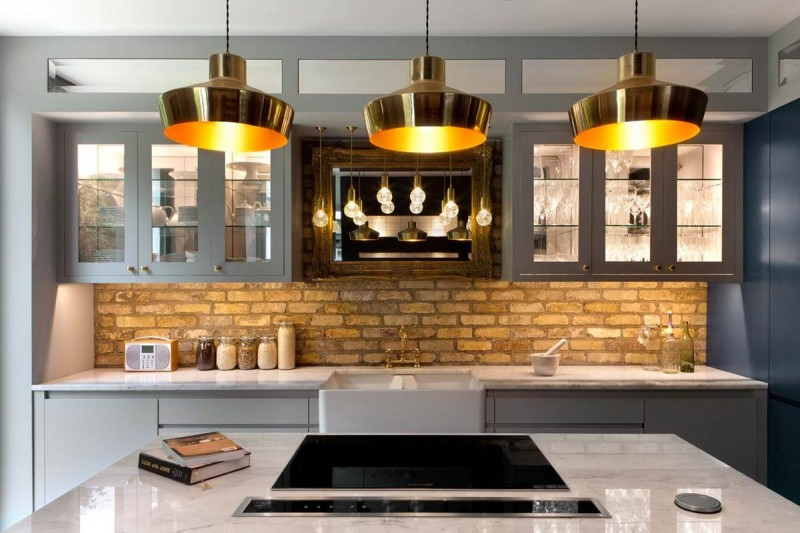 brass pendants, white island, white cabinet, open brick backsplash
