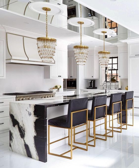 chandelier pendants on gold and crytal look, white black marble island, black cushion stool with golden legs, white wall, white cabinet, white floor