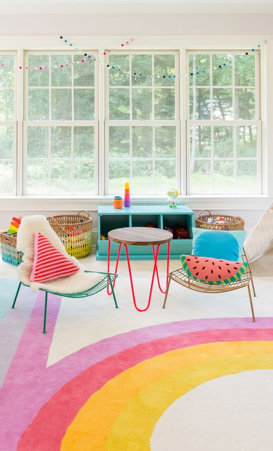 children's room, white wall, windows, low colorful chairs, low side table, rattan baskets, tosca shelves, white rug with colorful lines