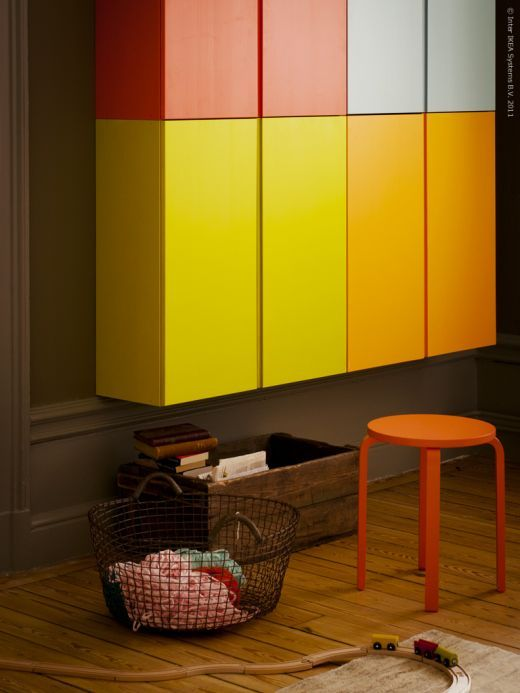 colorful floating ivar cabinet on the wall, wooden floor, stool, basket, wooden box