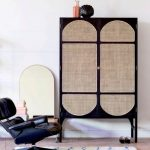 Dark Wooden Cupboard With Rattan On The Door, Legs, Wooden Floor, White Wall, Chair