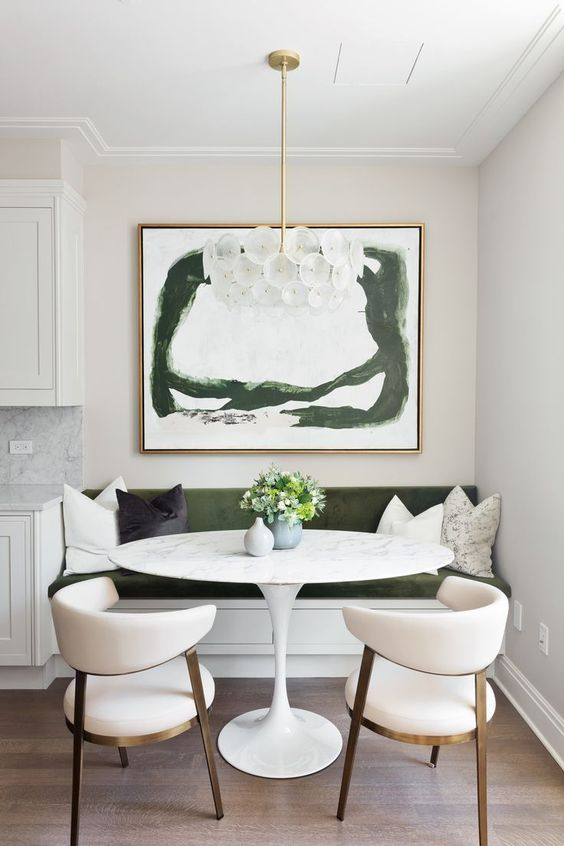 dining nook, wooden floor, white chairs with round back, white bench with green cushion, pillow, chandelier, wall painting