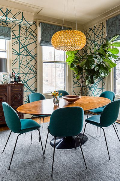 dining room, grey rug, white teal wallpaper, wooden floor, brown wooden cabinet, wooden round dining table, teal chair, yellow glass round pendants