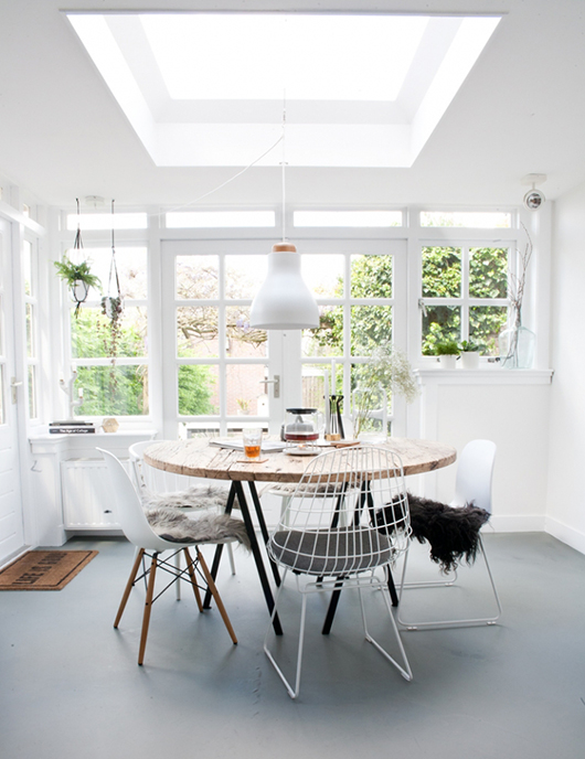 dining room, light grey flooring, white wall, white ceiling, white modern chairs, wooden round table, white pendant, hanging plants