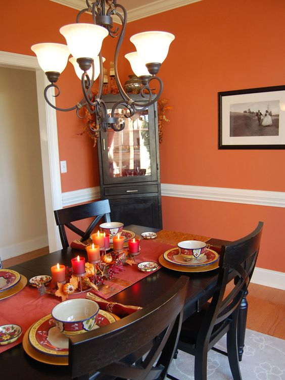 dining room, orange wall, molding in the middle, black wooden dining table set, marble chandelier, black cabinet