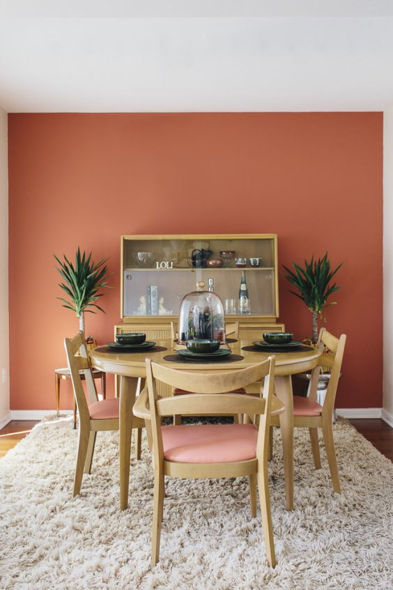 dining room, wooden floor, beige rug, light wooden dining set with pink cushion, light wooden cabinet, side table, plants, pink terracotta accent wall
