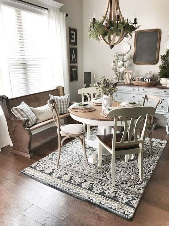dining room, wooden floor, rug, round wooden table, off white wooden chairs, wooden bench, wooden cabinet, white wall, wooden chandelier