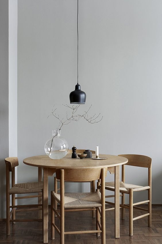 dining room, wooden floor, white wall, round wooden dining table, wooden dining chairs with rattan seating, black pendant