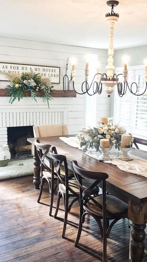 dining room, wooden foor, wooden square table, wooden chairs, white chair, chandelier, white ceiling, white wood planks wall, fireplace