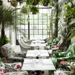 Dining Tables With White Square Table, Colorful Chairs With Leaves And Flowers Patterns, Plants On Floor, Wall, And Ceiling, Glass Windows