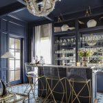 Elegant Bar, Pattern Flooring Tiles, Black Bar Island With Beige Top, Black Shelves, Acrylic Stool With Golden Legs, Chandelier