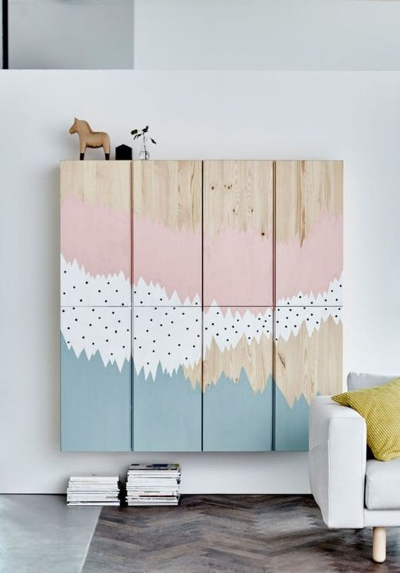 floating ivar cabinet with artistic pink, white, blue colors on white wall, grey floor, white sofa