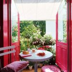 Front Door On Balcony, White Round Table, White Chair, Red Pillows, Plants, Rattan Rug