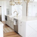 Glass Pendants With Golden Geometric Cage, White Island, White Sink With Golden Faucet, Wooden Floor, White Wall