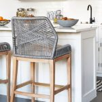 Grey Woven Stool On Wooden Egs, Brown Cushion, White Island, Grey Floor, White Subway Tiles