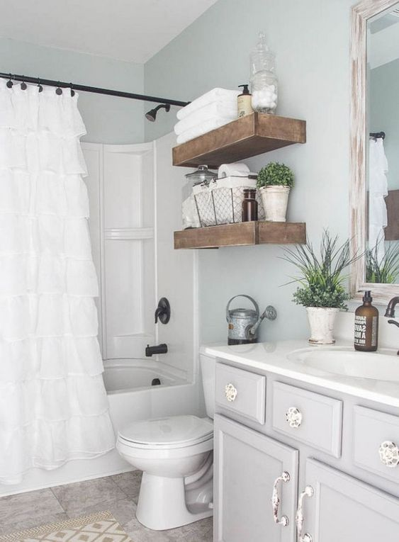 guest bathroom, patterned floor tiles, white tub, white toilet, white curtain, white elegant vanity, white sink, wooden framed mirrror, floating shelves