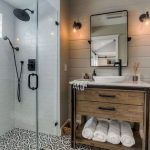 Guest Bathroom, White Wooden Planks Wall, Patterned Floor Tiles, Shower Area, Glass Partition, White Toilet, Wooden Vanity With White Marble Top, White Sink, Mirror, Sconces