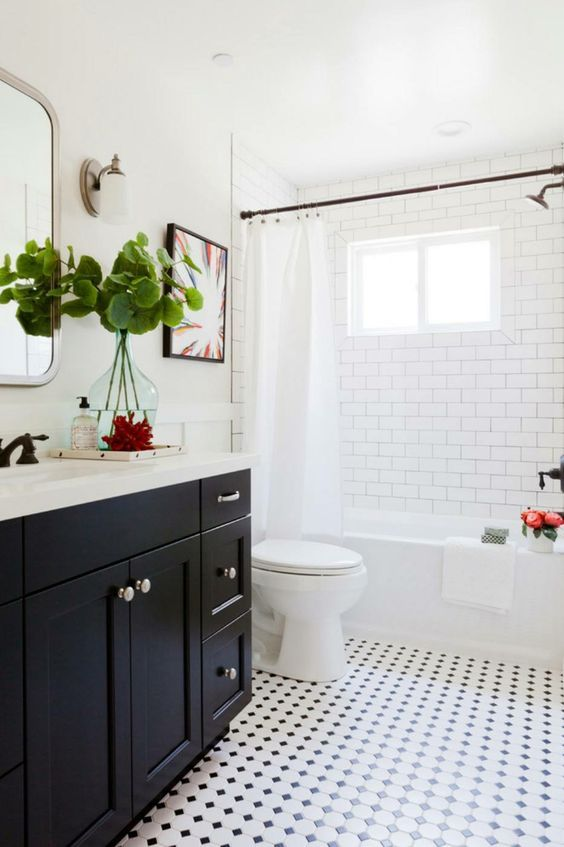 guest bathroom with white subway wall tiles, tiny white black geometric floor tiles, white tub, white toilet, white wall, black wooden vanity with white top, mirror, white curtain