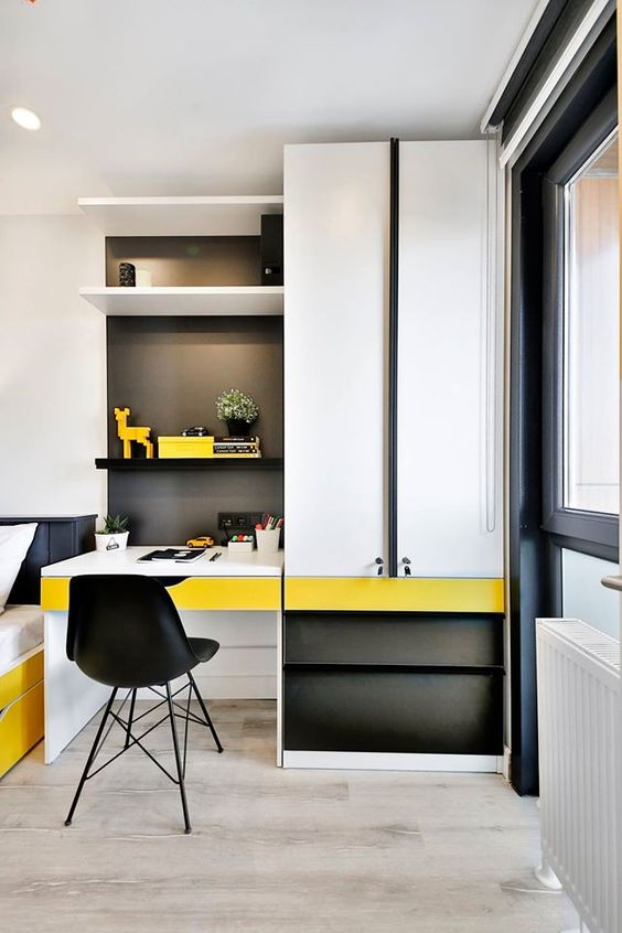 home office area with white tall cabinet, floating shelves, black background, black cabinets, yellow drawer, black modern chair