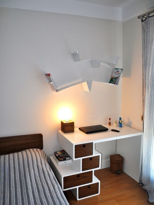 home office corner, wooden floor, white table with randomly zigzagged drawers, unique floating shelves, table lamp